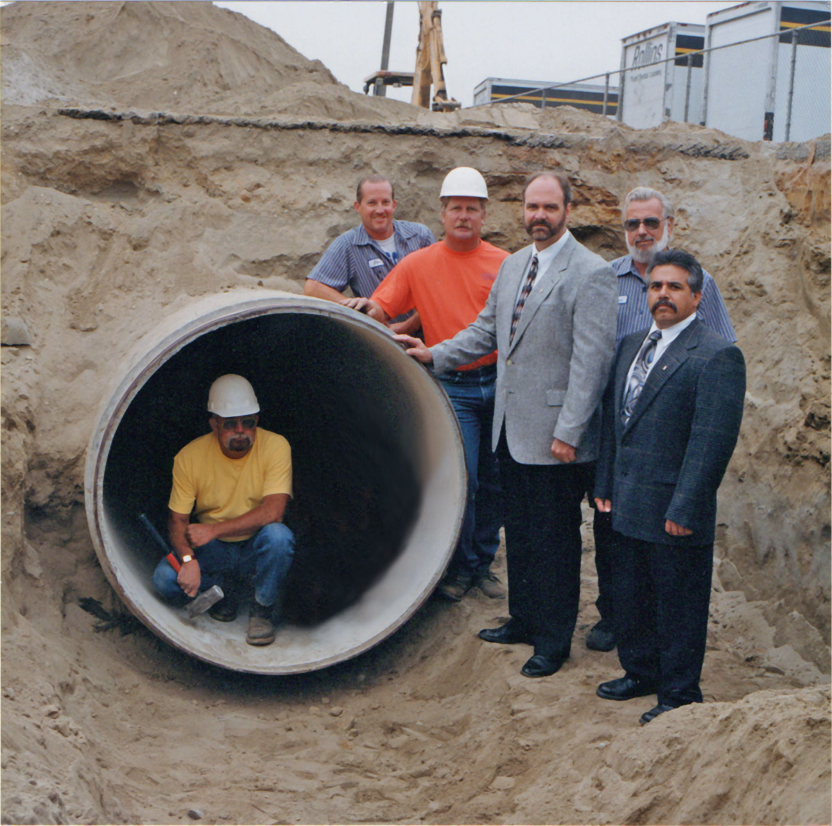 Photo op of staff, management and a worker kneeling in a large pipe under construction, circa 1990's.