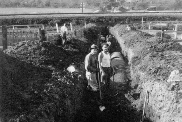 Photo op of two workers standing in a large ditch with sections of pipe under construction, circa 1950's.
